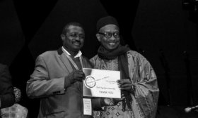 Ogo Doumbo (left) is recognised for his contribution to the malaria community at the MIM 2018 conference in Dakar, Senegal.