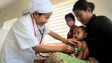 medic examines infant, Cambodia