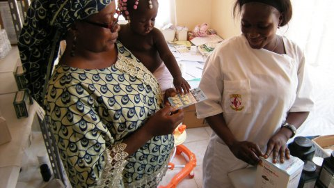 A mother and child receiving malaria medication in Angola